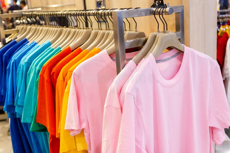 Colorful t-shirt on hangers for sale stock images