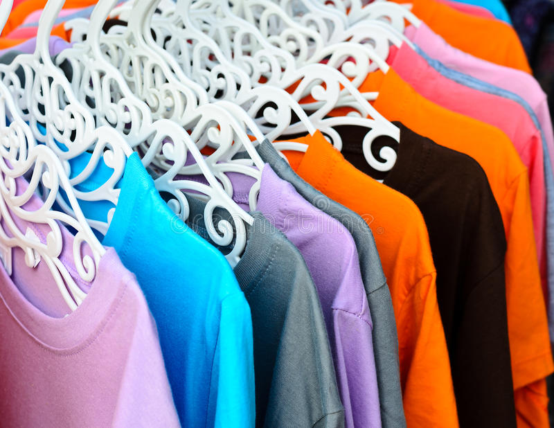 Colorful t-shirt on hangers stock photos