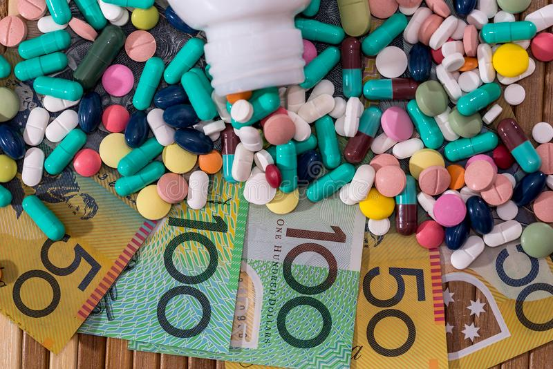 Tablets with container and australian dollars. Colorful tablets with container and australian dollars royalty free stock image