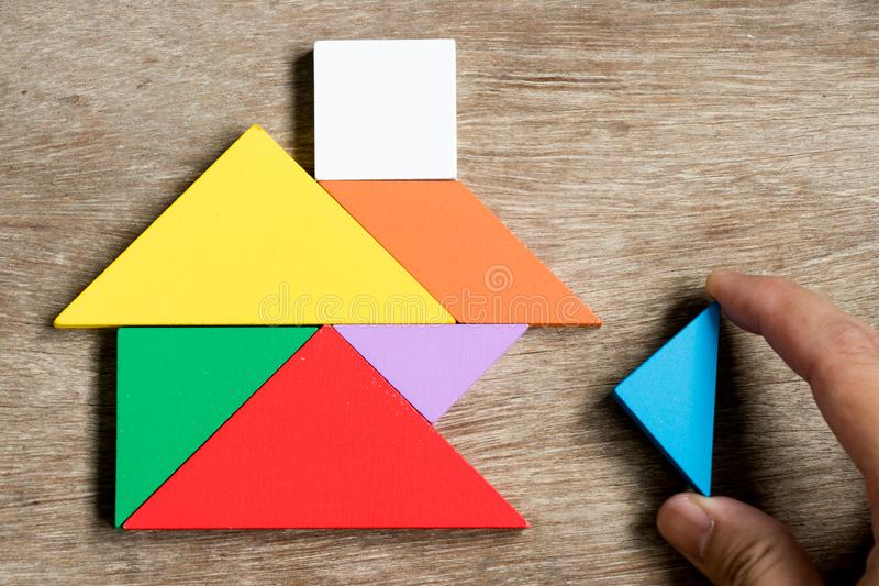 Colorful tangram puzzle in home shape wait for fulfill. On wood background Concept for build dream house, happy family life, property investment stock photography