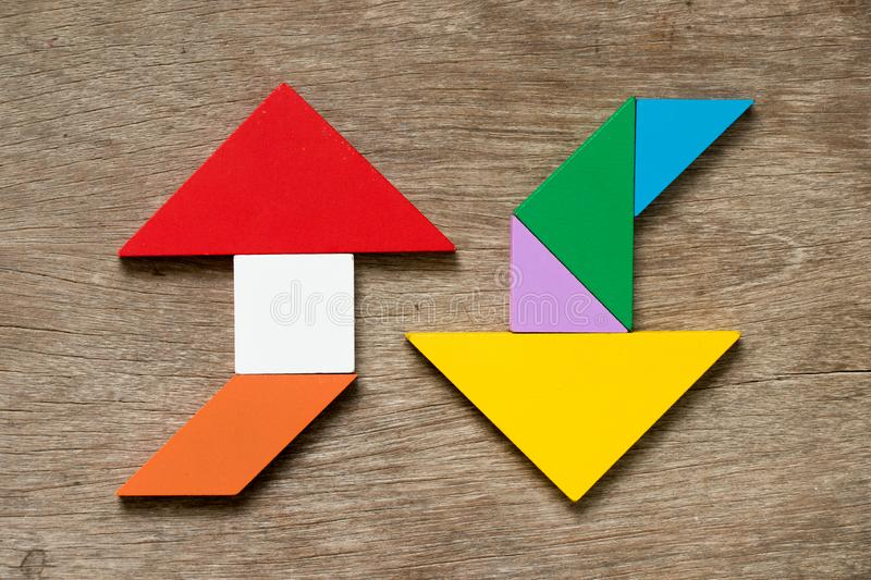 Colorful tangram puzzle in upward and downward arrow shape. On wood background royalty free stock photos