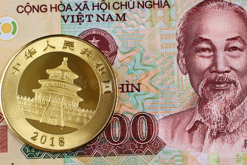 A Vietnamese ten thousand bill with a Chinese gold coin royalty free stock images