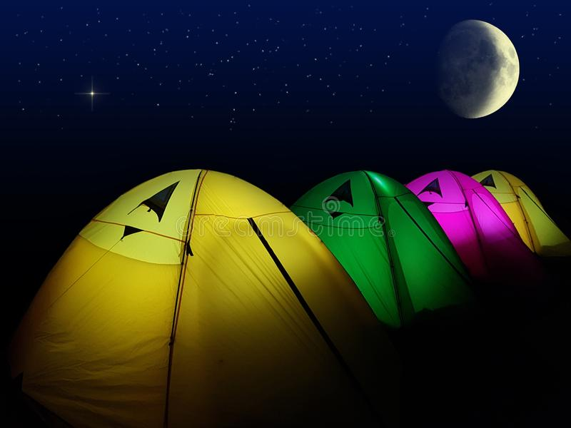 Colorful tent glows under a night sky with moon and full of star stock photography