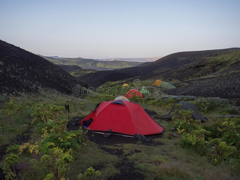 Colorful tents in Botnar campsite at Iceland on Laugavegur hiking trail, green valley in volcanic landscape among lava. Fields with view on Myrdalsjokull royalty free stock image