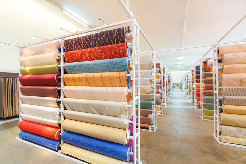 Colorful textile fabric material rolls in warehouse stock image