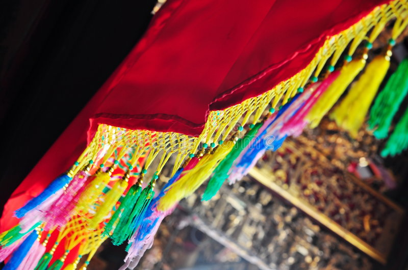 Colorful threads in motion. Colorful threads hanging from a red cloth in motion royalty free stock image