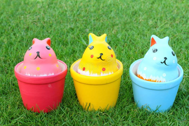 Colorful three rabbits in ceramic cups on grass background. Colorful rabbits in ceramic cups on grass background stock photos