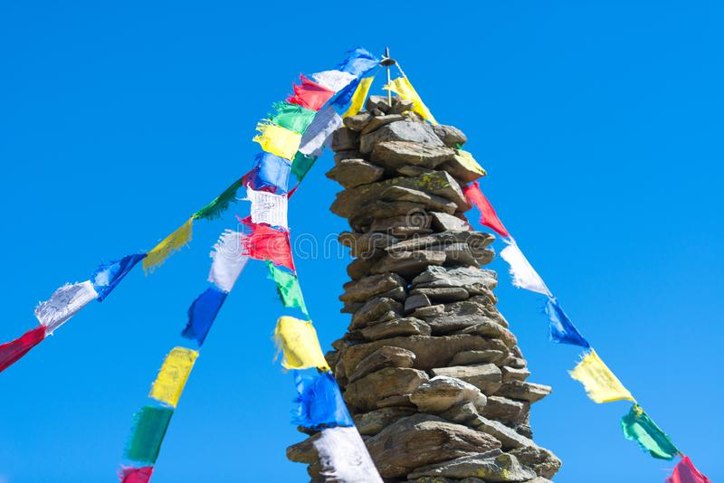 Colorful Tibetan Buddhist prayer flags hanging on a stone pile o royalty free stock photos