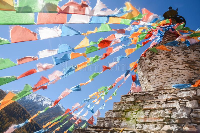 Colorful tibetan flags and snow mountain at Siguniang scenic area in China. Colorful tibetan flags and snow mountain at Siguniang scenic area in autumn season royalty free stock image