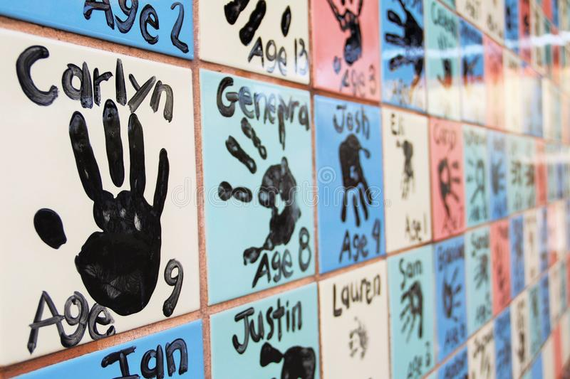 A Colorful Tiled Wall with Children`s Handprints royalty free stock photo