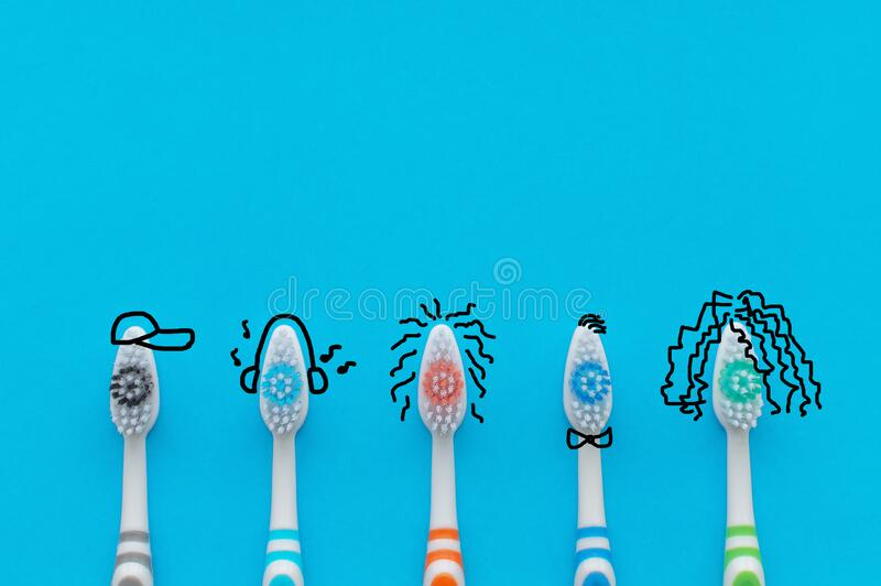 Colorful toothbrushes on a blue background in the form of cartoon characters. The view from the top. Close up. Concept of family. Hygiene stock images