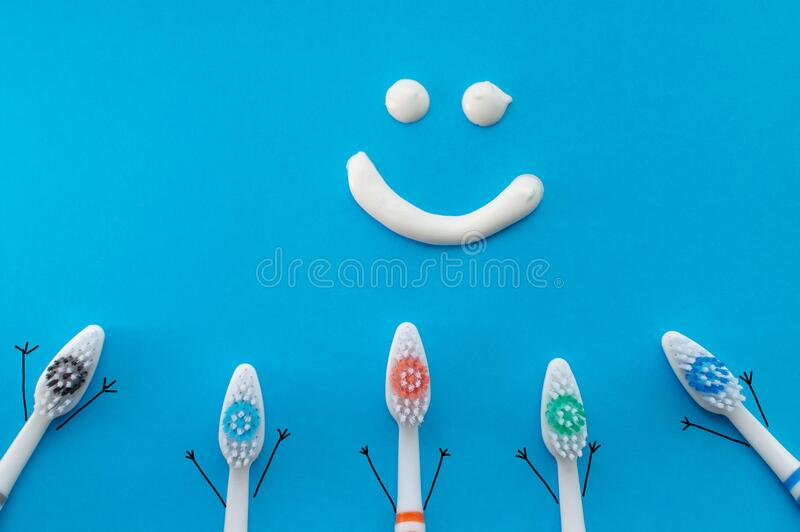 Colorful toothbrushes in the form of cartoon characters on a blue background with a smile drawn with toothpaste. The view from the. Top.The concept of family stock photo