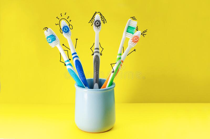 Colorful toothbrushes in the form of cartoon characters in a blue glass on a yellow background. The concept of family hygiene royalty free stock images