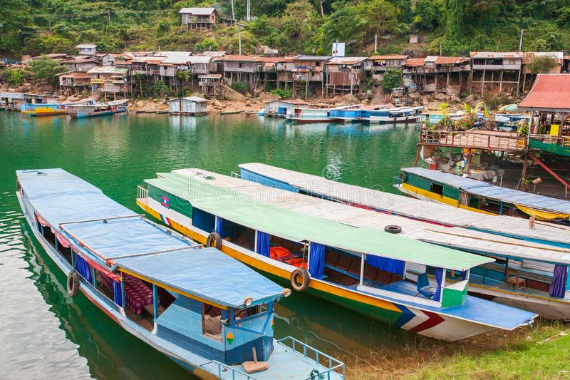 Colorful tourist boats on Nam Ngum Lake, Pier, raft, and floating house background. Top tourist attractions in Laos. Vientiane Pr. Ovince. Soft sunlight. Rainy royalty free stock photography