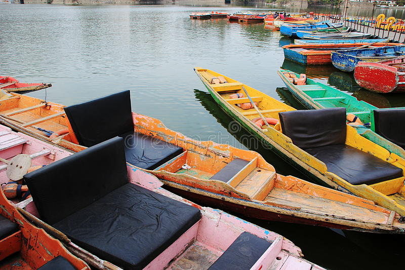 Colorful Tourist Row Boats. Attractive, colorful row boats waiting for tourists at Nakki Lke, Mount Abu, Rajasthan, India, Asia royalty free stock image