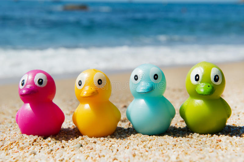 Colorful Toy Ducks  At Beach Stock Photos