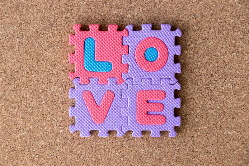 Colorful toy foam alphabet in word love on cork board background royalty free stock photography