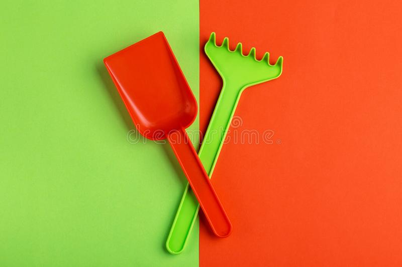 Colorful toy spade and rake on bright background royalty free stock photography