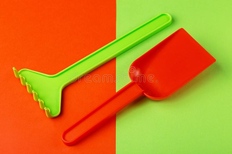 Colorful toy spade and rake on bright background royalty free stock images
