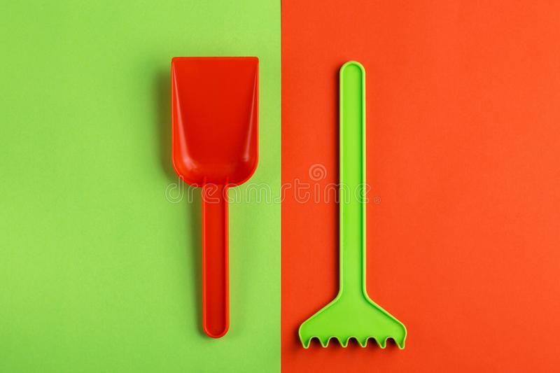 Colorful toy spade and rake on bright background stock images