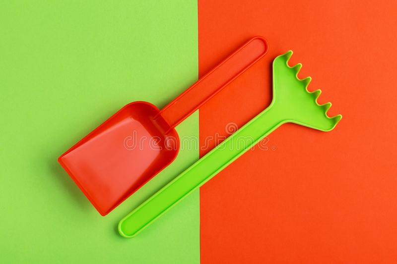 Colorful toy spade and rake on bright background stock photo