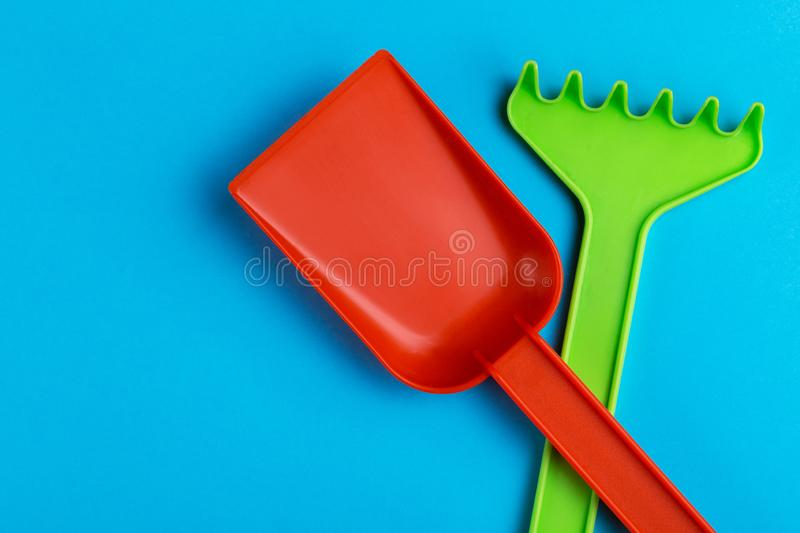 Colorful toy spade and rake on bright blue background stock photography