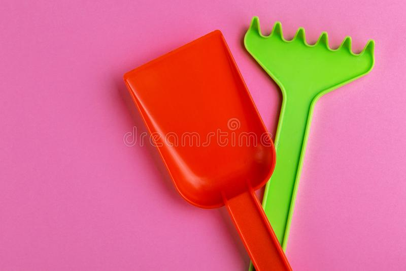 Colorful toy spade and rake on bright pink background stock images