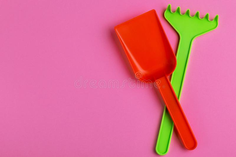 Colorful toy spade and rake on bright pink background stock photography