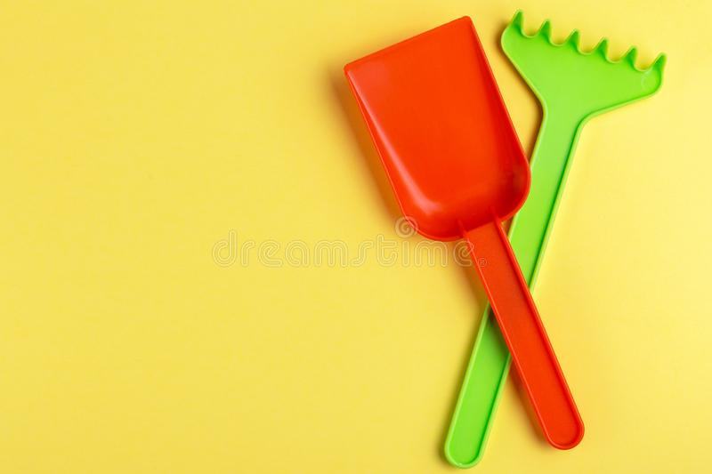 Colorful toy spade and rake on bright yellow background royalty free stock photo