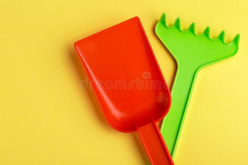 Colorful toy spade and rake on bright yellow background stock photography
