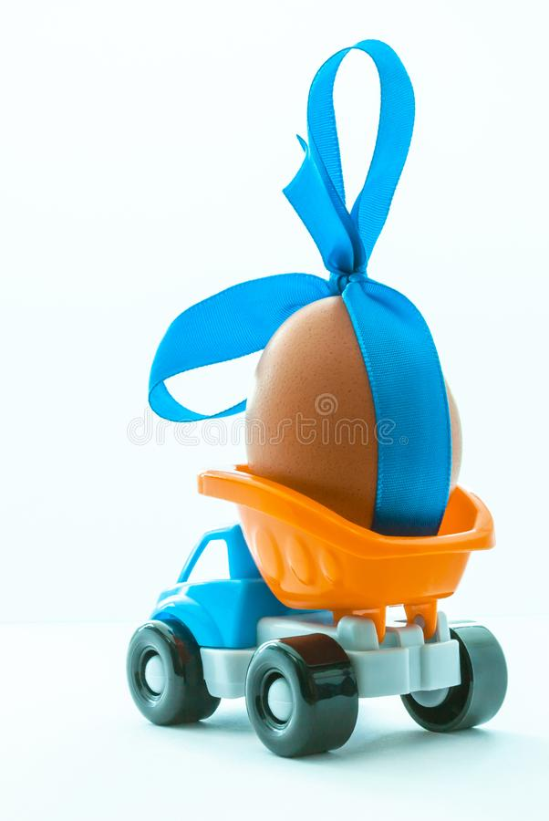 Colorful toy truck with a chicken egg in the back on a white background, side view stock photos