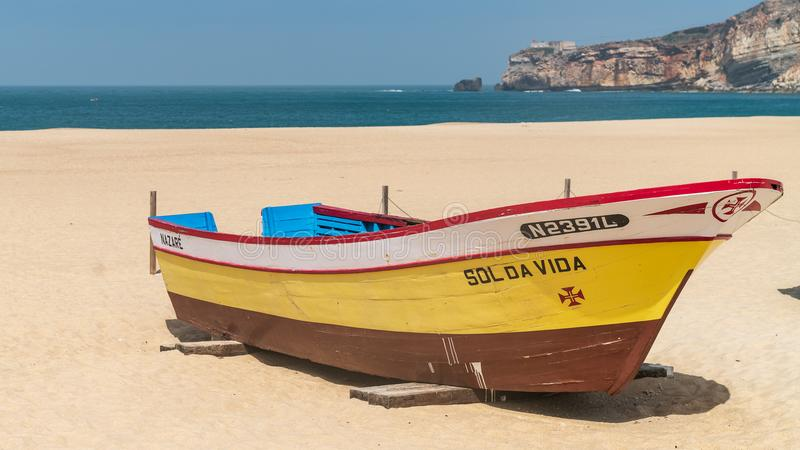Colorful traditional old wooden fishing boat on the beach of fishing village of Nazare royalty free stock images