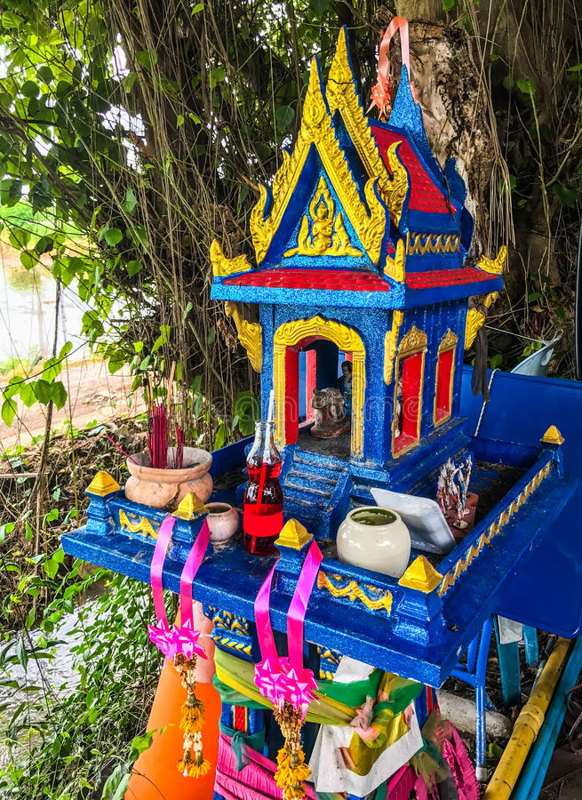 Colorful Traditional Thai outdoor spirit house shrine with flower garlands under the tree shade stock photo