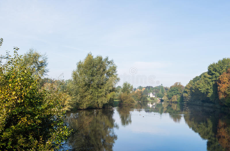 Colorful trees at the banks of a river. Colorful trees reflected on the mirror smooth surface of the river on a sunny morning in the early autumn season royalty free stock photography
