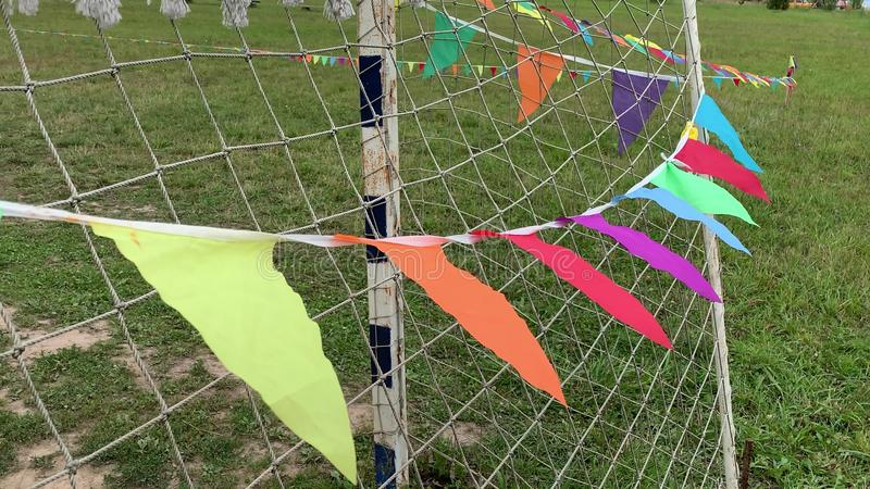 Colorful triangle flags on the string waving in the wind on a soccer field near the gate during sport festival royalty free stock photography