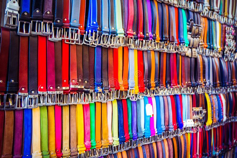 Colorful trouser leather belts hang in a row for sale on market in Florence, Firenze, Tuscany, Italy royalty free stock photography