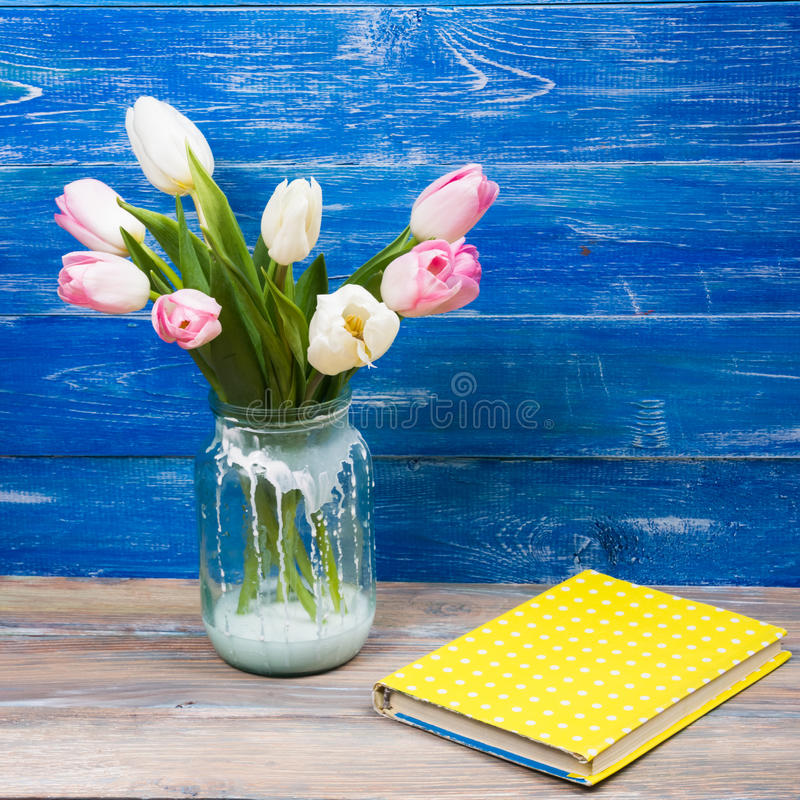 Colorful tulips flowers and yellow book on blue wooden desk table background. Copy space. Beautiful pink flowers tulips on blue wooden desk table. Copy space stock photo