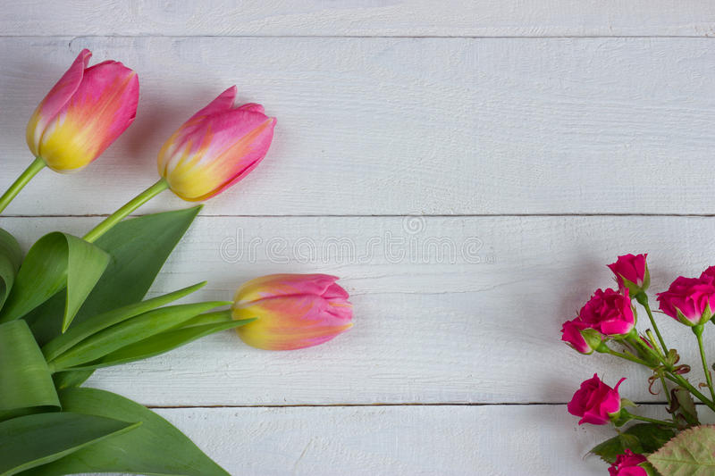 Colorful tulips with miniature roses on wooden table. Top view with copy space stock image