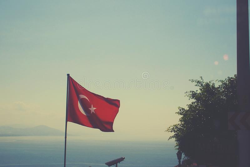 Turkish flag waving in the wind on a summer warm day against the sky. Colorful Turkish flag waving in the wind on a summer warm day against the sky stock photo