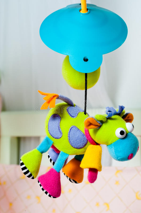 Download Colorful Turning Cow Baby Toy Over The Bed Stock Image - Image: 26550987