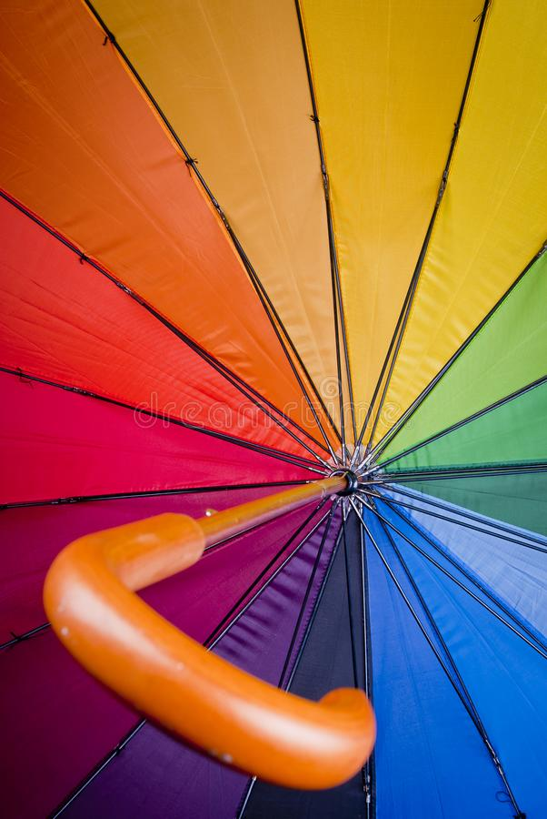 Colorful umbrella from inside. Colorful umbrella close up shot from inside the handle is in the foreground