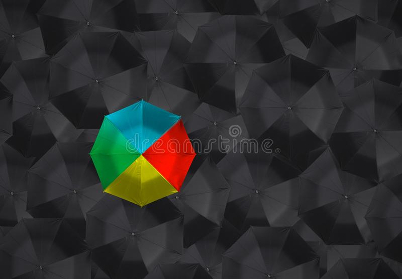 Colorful umbrella and many black umbrellas. stock photos