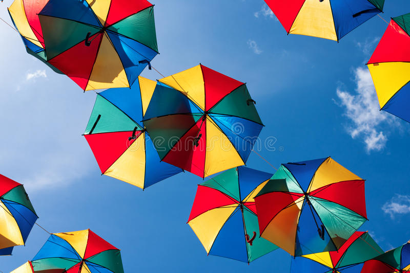 Colorful umbrellas background. Coloruful umbrellas urban street decoration. Hanging Multicoloured umbrellas over blue. Sky royalty free stock image