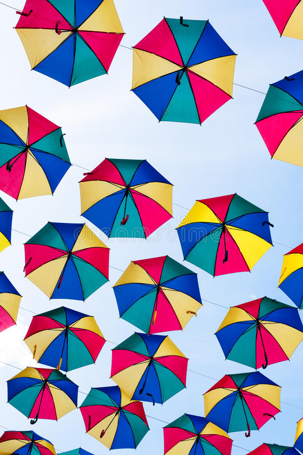 Colorful umbrellas background. Coloruful umbrellas urban street decoration. Hanging Multicoloured umbrellas over blue. Sky stock photo