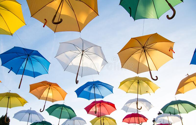 Colorful umbrellas flying in sky royalty free stock image