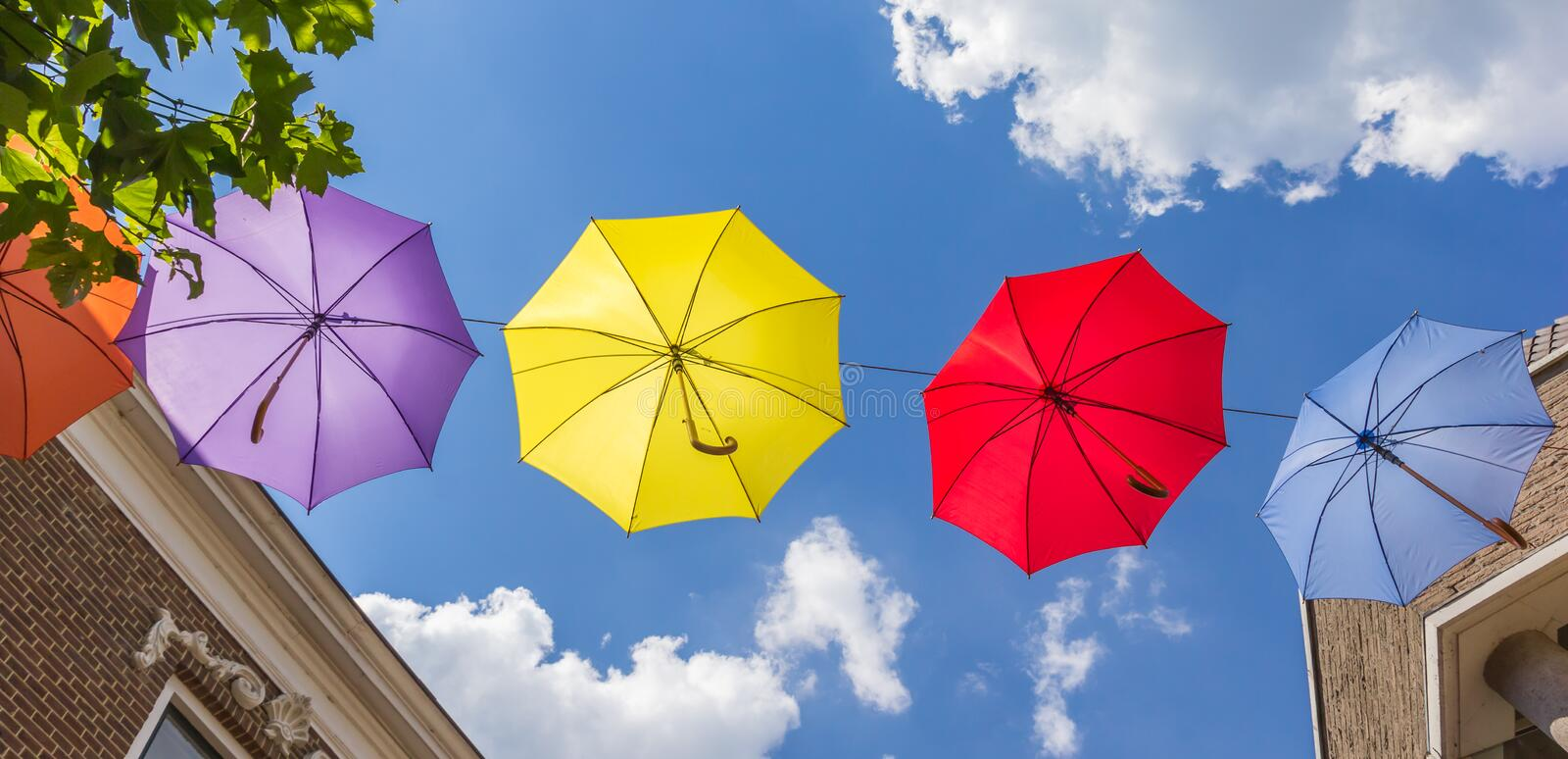 Colorful umbrellas hanging between buildings in Lochem. Netherlands stock photography