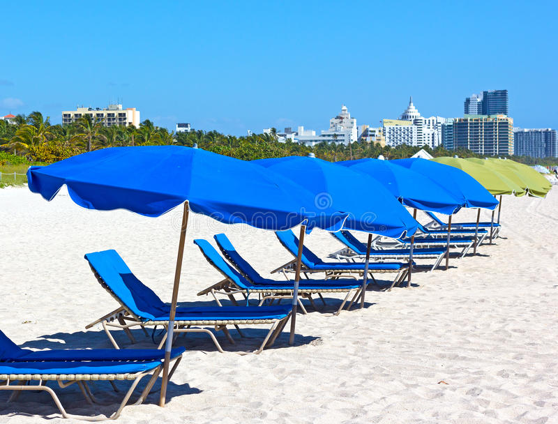 Colorful umbrellas and lounge chairs on Miami Beach with visible city skyline. stock photo