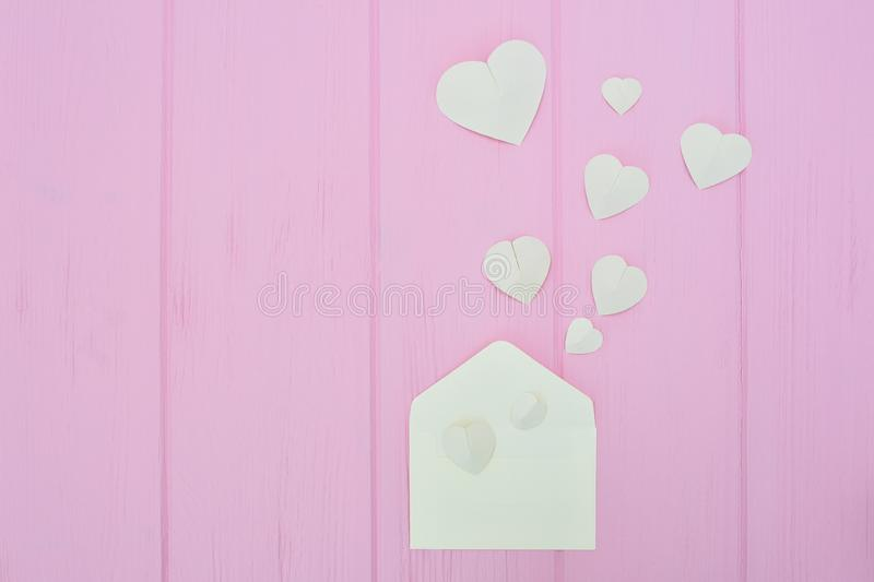 Colorful Valentine Day greeting card envelopes with heart. White hearts pours out of the envelope on pink wooden. Background. Hearts fly out from the envelope stock photo
