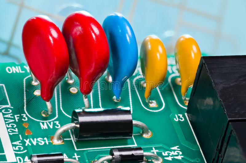 Colorful varistors. Circuit board detail. Electronic components for surge protector stock image