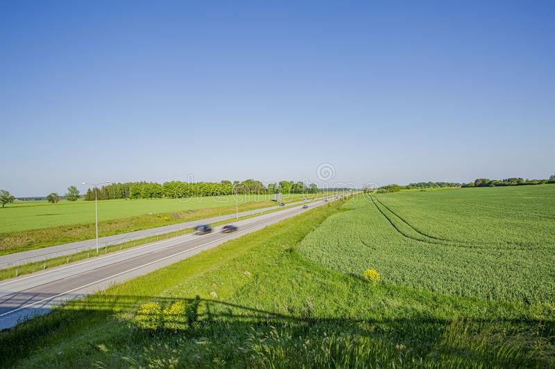 Colorful view from above on highway road with several cars. Side green fields and blue sky on bright summer day. Beautiful nature background stock image